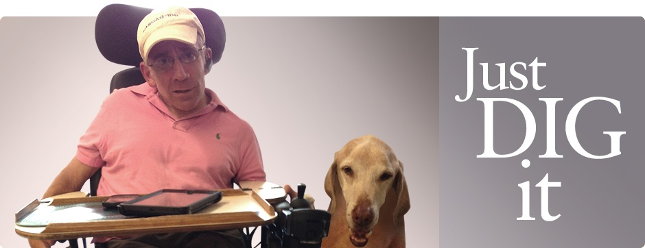 A man on a wheelchair, with his dog next to him.