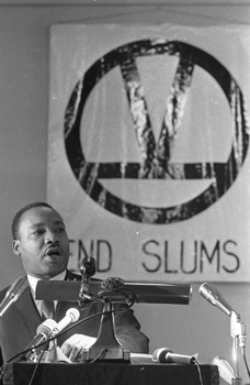"Martin Luther King Jr. with a sign that says ""End Slums"""