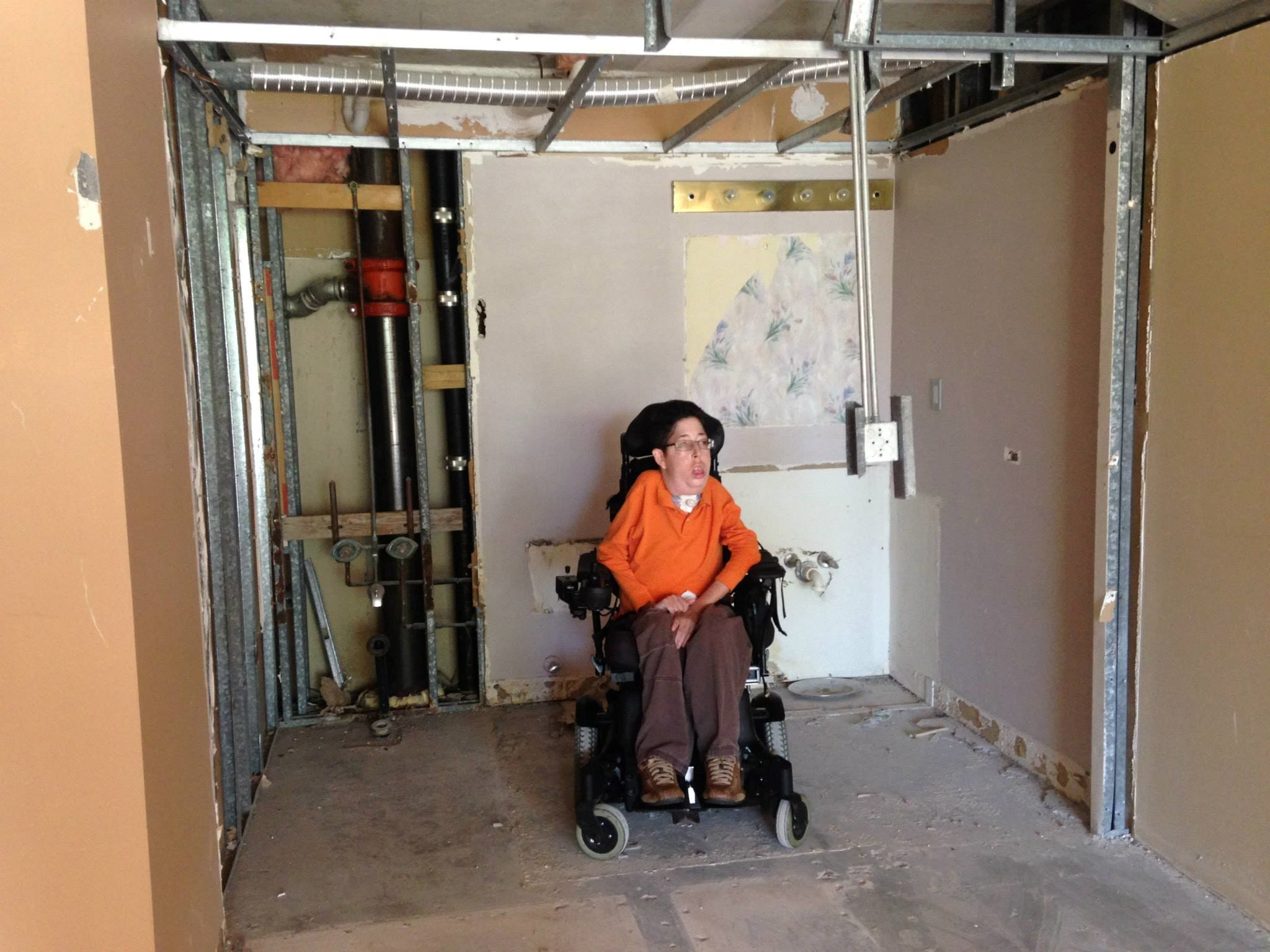 picture of Zachary Trautenberg in a motorized wheelchair in a home under constrution