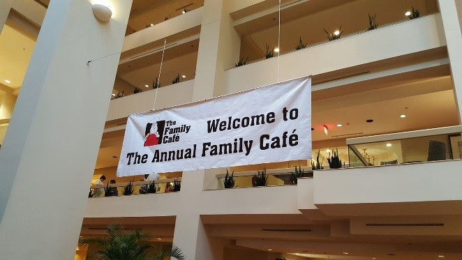 """A banner hangs from inside a multiple-story building that has a man in a chef's hat (the Family Cafe logo) and the words """"Welcome to the Annual Family Cafe"""""""")"""