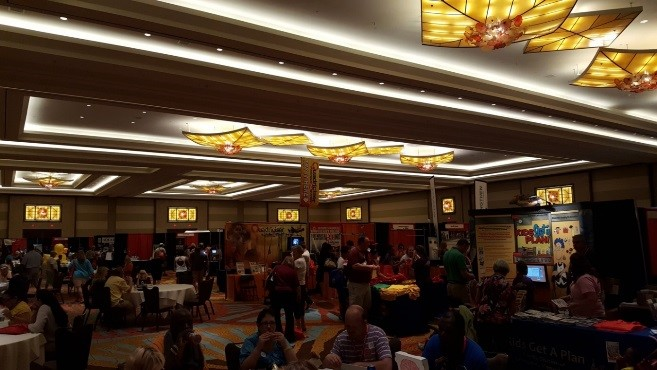 Many people stand and sit and are scattered around a large room that has many display posters standing up on tables