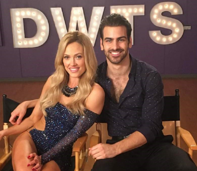 "Nyle DiMarco and Peta Murgatroyd from Dancing with the stars Season 22 sit next to each other and smile in front of lit up letters ""DWTS"""