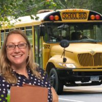 Stephanie Langer standing with a file in front of a school bus in a home made photoshopped picture