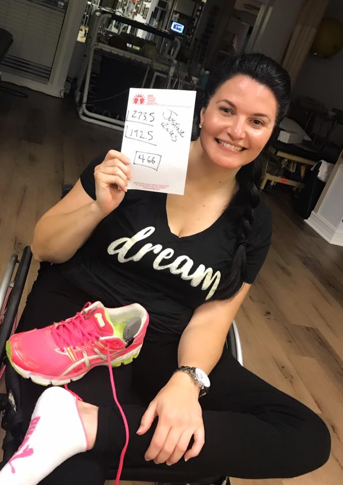 Justine sitting in her wheelchair with a pink sneaker in her lap holding a paper in her hands