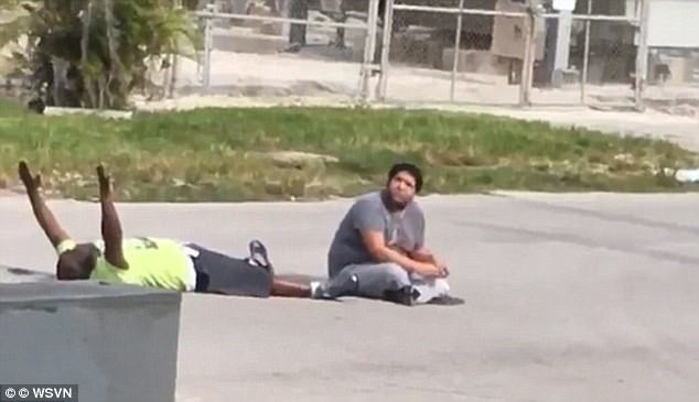 Arnaldo RIos Soto sitting in the middle of the street with charles kinsey lying down on the ground next to him