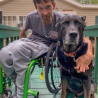 Albert Schaw, a man in a bright green manual wheelchair wearing grey pants and a grey t-shirt about 20 years old with brown hair and a beard with his left arm around a huge black hound, great dane mix that is the same height as Mr. Schaw when he crouches in his wheelchair.