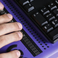 Braille Purple Keyboard with hands on it for Voting