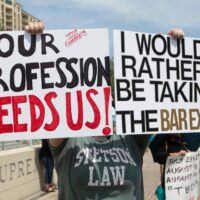 law students protesting in front of the supreme court with signs that says our profession needs us and I would rather be taking the bar exam