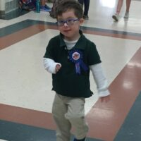 little boy with Down syndrome wearing a blue shirt and brown pants and blue glasses with a pin that says Birthday boy