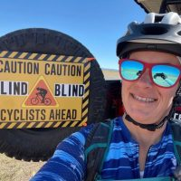 Shawn Cheshire in arizona with her bike helmet blue shirt and red reflective sunglasses with the reflection of her taking a selfie. Shawn is smiling and in the background is the tire from her vehicel with a sign that says Caution Blind Cyclists Ahead. the desert is in the background.
